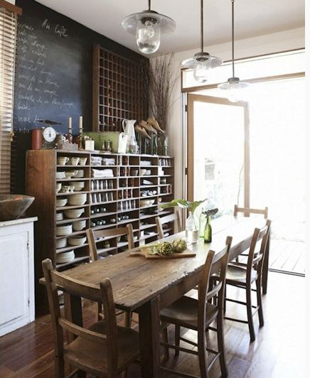 kitchen storage/dining long wood table/chairs, open shelving stocked with white dishes, chalkboard,
