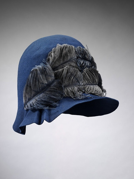 Cloche hat | Made in London for Liberty, 1928 | Materials: felt and ostrich feathers, lined with silk taffeta |  This cloche hat was worn as part of an ensemble by Marian Hazel Lasenby for her wedding to William Moorcroft in 1928 | The close-fitting cloche hat was extremely popular at the time. A simple modern design, it was an easy to wear unfussy style of hat which fitted snugly over fashionably closely-cropped hairstyles | VA Museum, London