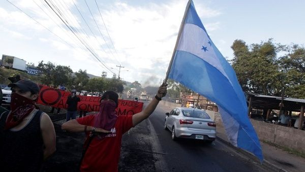 Opposition supporters sing Honduras' national anthem at a barricade during a protest after the U.S. backed the re-election of Honduran President Juan Orlando Hernandez, in Tegucigalpa, Honduras December 27, 2017. | Foto: Reuters
