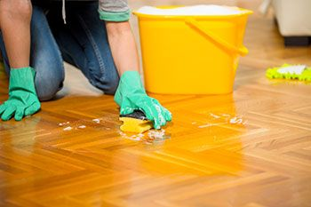 Person mopping floor with rubber gloves and sponge