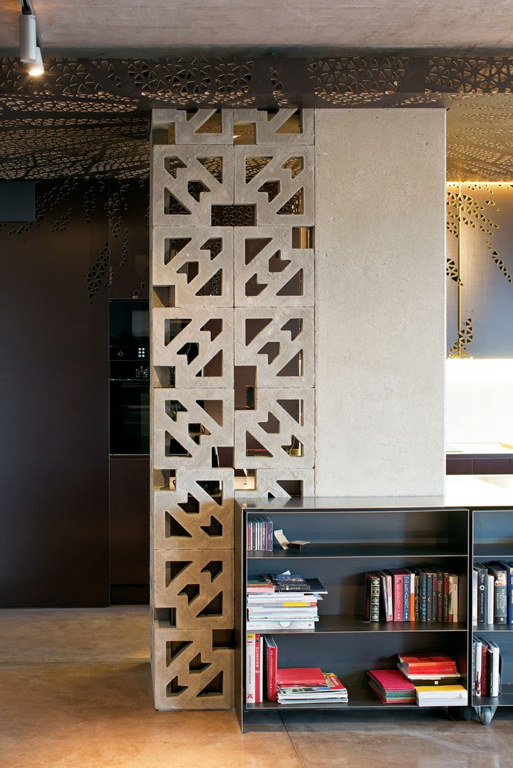 Ornate concrete blocks screen a storage area in the kitchen while letting  light through. The