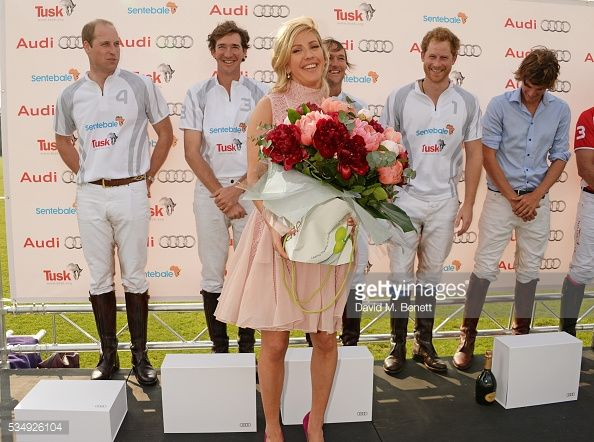 Ellie Goulding is presented with flowers as players Prince William, Duke of Cambridge, Luke Tomlinson, Mark Tomlinson, Prince Harry and William Melville-Smith attend day one of the Audi Polo...