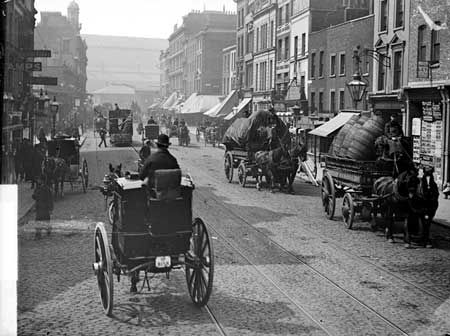 "Kings Cross, Islington, Greater London c. 1885 ""Reproduced by permission of English Heritage.NMR Reference Number: CC97/01265	   Caption:	A busy street view with people and horse-drawn vehicles including a Hansom cab in the foreground.  Photographer:	 York and Son"""