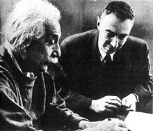 Einstein writing at a desk. Oppenheimer sits beside him, looking on.