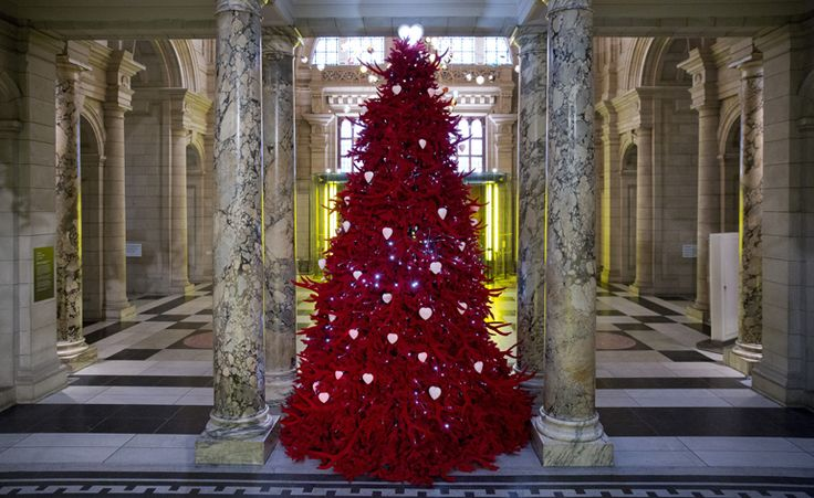 I love trees that aren't green!   V&A, London:  This year artists Helen and Colin David were commissioned to customise the V&A's holiday tree, with the mouth-watering result: 'Red velvet tree of love' lighting up the museum's marble entrance. Although traditional in silhouette, it is in fact coated in red flocking and decorated with 79 sets of hand cast replica antlers along with 67 white, heart-shaped 3D printed baubles, standing at an impressive 4.75 meters high