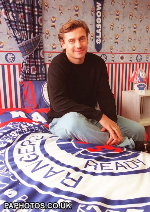 Andrei Kanchelskis from Fiorentina, sits in a bedroom/shrine to Rangers, in Glasgow, after he was signed up with Rangers FC for 5.5million today (Weds). The 29-year-old Ukranian becomes new coach Dick Advocaat's fifth summer signing and takes the Ibrox outfit's spending over the 20million mark. Photo by David Cheskin.