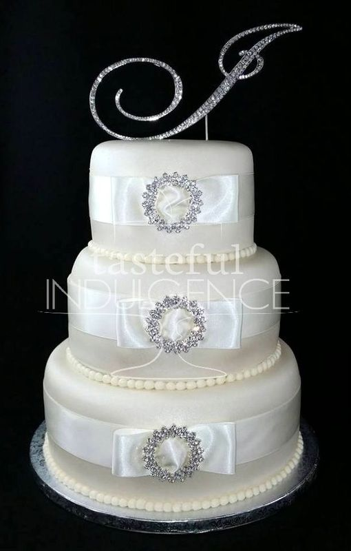 A 3 Tier Ivory Fondant Wedding Cake Accented With Coordinating Ribbons