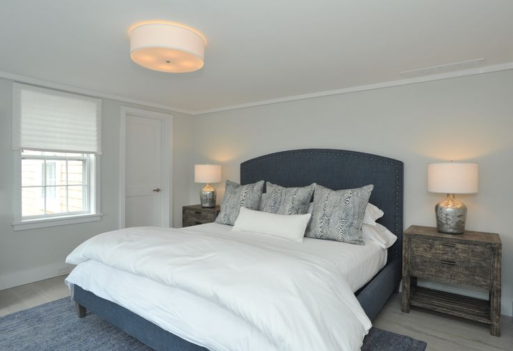 This guest room follows the nautical yet modern theme of this Nantucket house with bright and airy whites accented by blue tones in the Lee Industries bed, faux bois pillows from Brunschwig & Fils and large rug. Mercury glass lamps sit atop the rustic bedside tables.