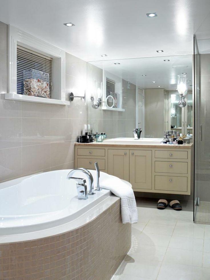 LYST BAD. Badet preges av duse farger, både på fliser og på baderomsmøblementet. Tak, vinduslister og gulvflisene er derimot holdt i hvitt. Det ovale badekaret er omringet av beige mosaikk, og i vinduskarmen står en glasskrukke med koraller fra Maldivene.