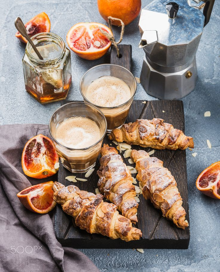 Traditional Italian style home breakfast. Latte in glasses, almond croissants and red bloody... - Italian style home breakfast. Latte coffee, almond croissants and red bloody oranges on dark wooden serving  board over concrete textured table, moka pot and honey jar at background, selective focus