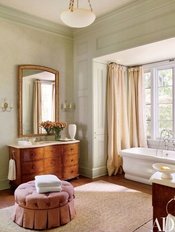 An alabaster pendant light by Vaughan hangs in the master bath, which has a Waterworks tub and a Victorian-style pouf by Hickory Chair | archdigest.com