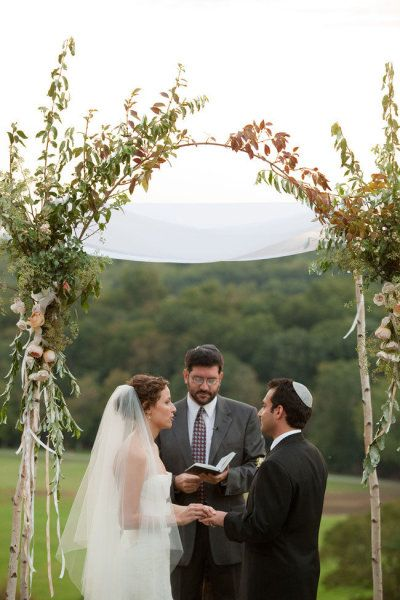 Saplings tied together to make an arch to make a beautiful background to the ceremony