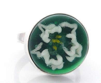 This is a handmade borosilicate glass cabochon set into a handmade sterling silver setting