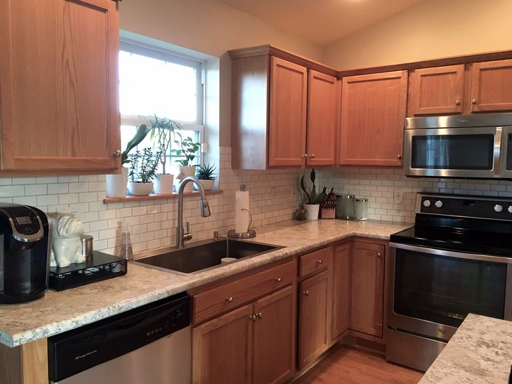 The feel of a white kitchen without white cabinets...Builder grade oak cabinets with high resolution laminate countertops (spring carnival) and white subway tile backsplash with light grey grout (lactic fete smoke grey)