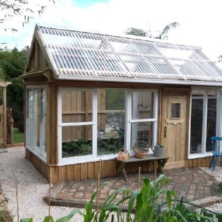 Greenhouse built with discarded windows and reclaimed wood doors. If your neighbors are replacing their windows...ask them for the old ones.  It will save them from the landfill and save you money!