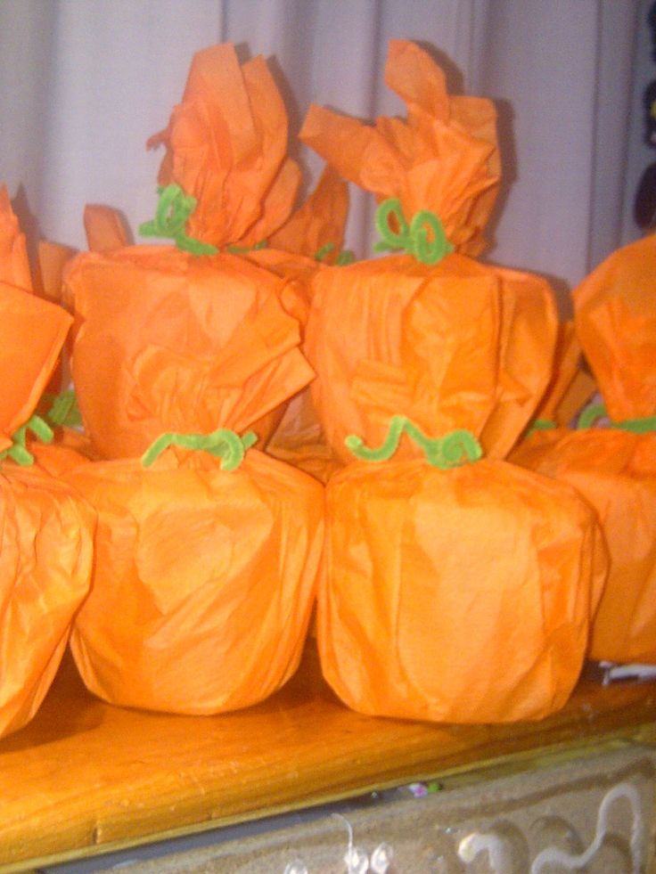 Goodie bags for a kid's halloween party.  Plastic tubs with lids wrapped in orange crepe paper and tied with a green chenille pipe cleaner.