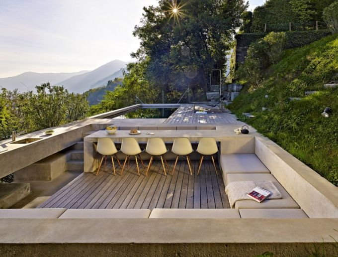 Terasa s venkovní kuchyní a bazénem je obklopena z jedné strany zelení a z druhé velkolepým prostorem zakončeným siluetou alp
