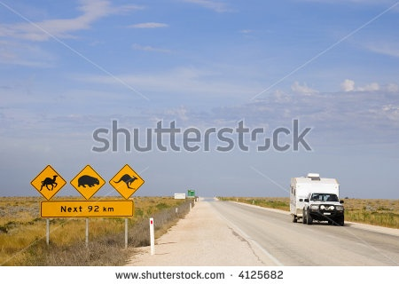 stock photo : Car and caravan on the Eyre Highway, Nullarbor Plain, South Australia, with iconic sign kangaroos, wombats, camels.