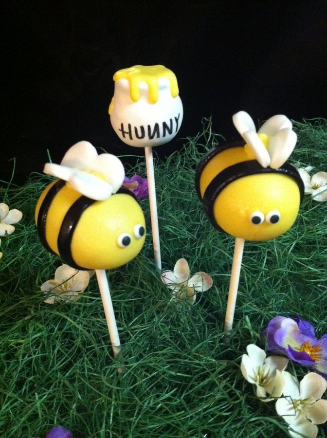 "Cake pops I did for a baby shower! The black stripes I did on the bees were fondant as well as the wings (used a heart cutter) eyes were candy. I shaped the honey pots before dipping them making a small indent at the top for the ""honey."""