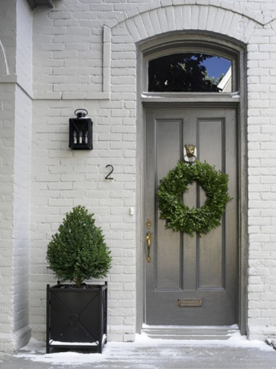 Small trees in planters on the stoop on each side of the front steps.  Good greenery for year round and can decorate with the holidays!