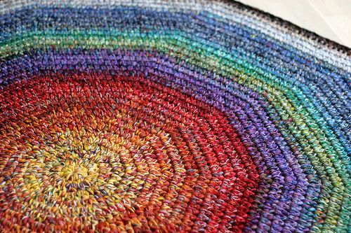 A basic pattern for a 10-sided rug out of large amounts of sock yarn scraps. The rug is crocheted with 8 strands of sock yarn held together -- it uses up yarn quickly.