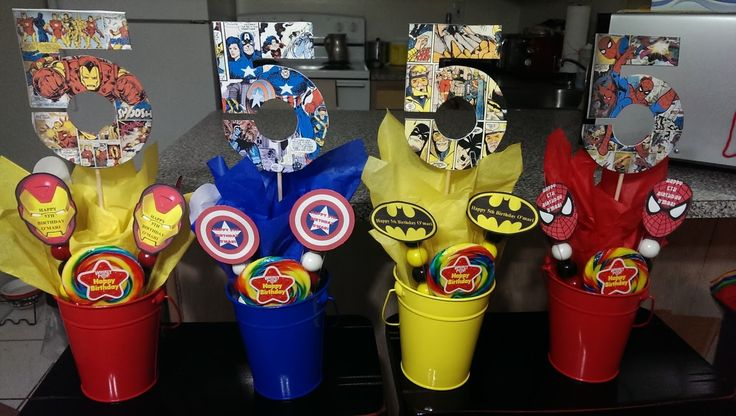 Comic Book Centerpieces I made for my son's 5th Birthday. The #5's are cardboard cut outs my husband did, I modpodge comic pages to them. The long plastic tubes have gumballs in them and lastly decorated with tissue paper and Superhero logo cut-outs