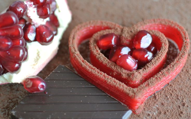 Two hearts printed in red chocolate ganache, dusted with cocoa powder, served alongside a piece of dark chocolate and pomegranate.