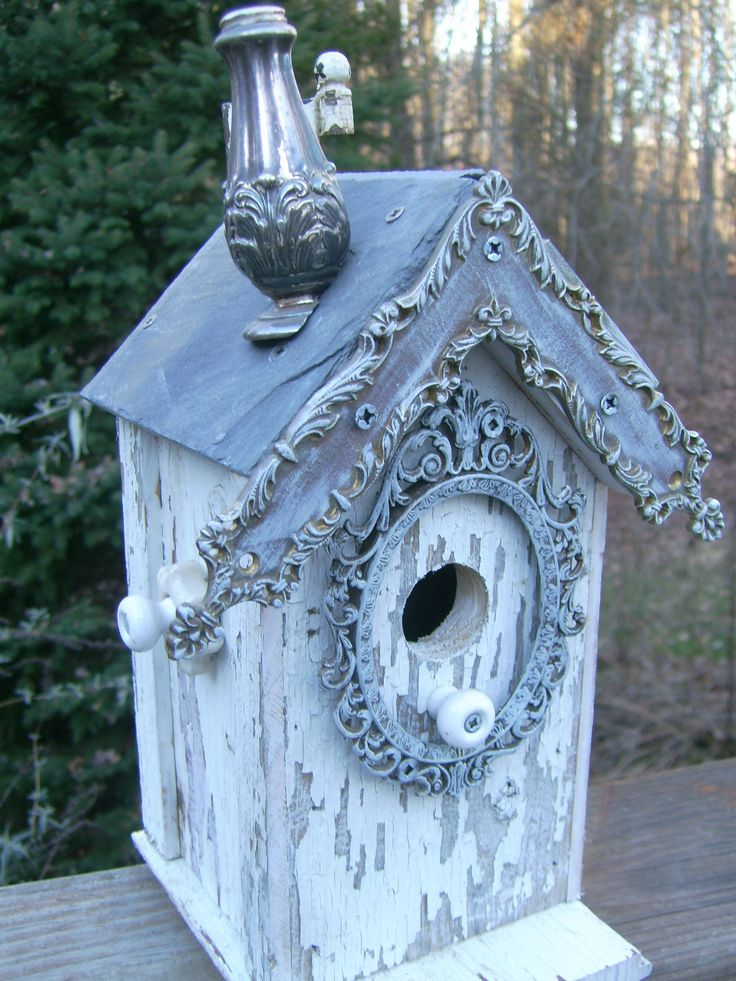 Shabby chic birdhouse with salt shaker chimney, picture frame around the hole and slate roof.