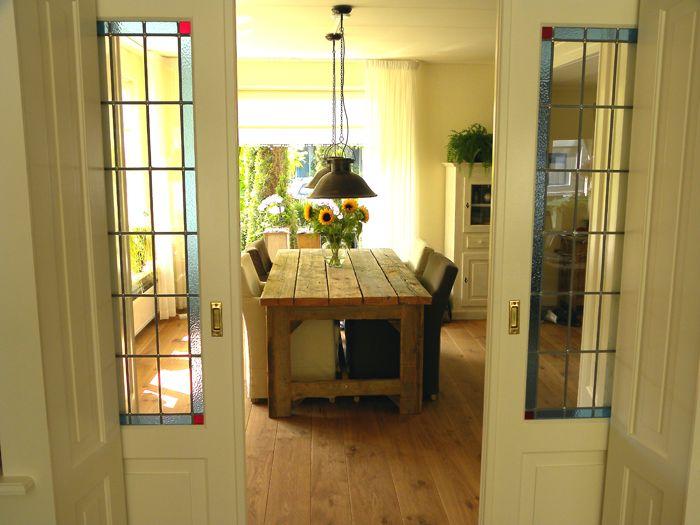 Glas-in-lood-schuideuren bij kamer-en-suite, evt. aan de zijwanden witte boekenkasten.