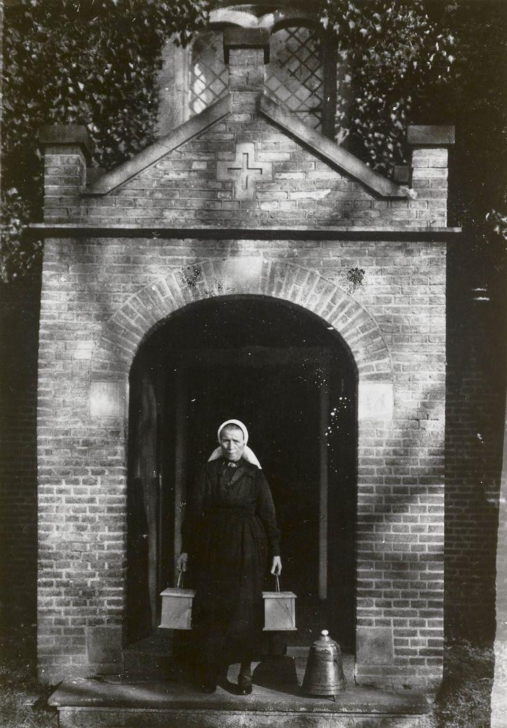 De stovenzetster uit Diepenheim in Twentse dracht 1943 De stovenzetster uit Diepenheim in Twentse dracht. De vrouw draagt een 'knipmuts' (cornetmuts). Ze staat in de toegang tot een kerk met in iedere hand een stoof. Naast haar staat een doofpot. #Overijssel #Twente #Saksen
