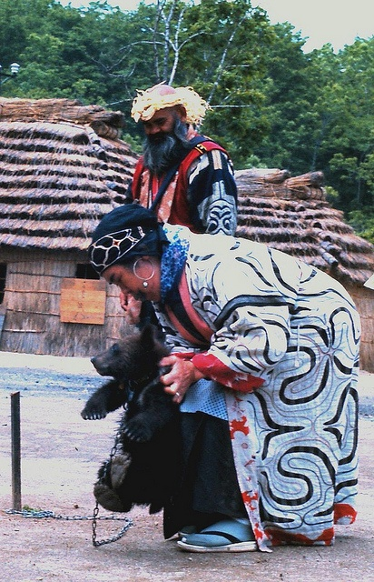 """Ainus with bear. (Japan)  """"Ainu"""" means """"human"""". These people regard things useful to them or beyond their control as """"kamuy""""(gods). In daily life, they prayed to and performed various ceremonies for the gods, including : """"nature"""" gods(ie. fire, water, wind and thunder) ; """"animal"""" gods, (ie. bears, foxes, spotted owls and gram-puses) ; """"plant"""" gods(ie. aconite, mush-room and mugwort) ; """"object"""" gods (ie. boats and pots) ; and gods which protect houses, gods of mountains and gods of lakes."""