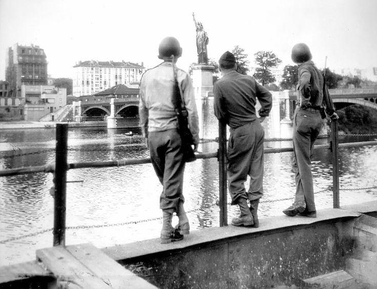 soldats américains admirant la réplique de la statue de la Liberté près du pont de Grenelle à Paris au moment de la Libération.