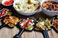 Ein Hauch von Öl: Weitere Raclette-Dinner-Party-Rezeptideen: Aufgeschnittenes Brot mit Nieselregen Olivenöl auf dem Grill.