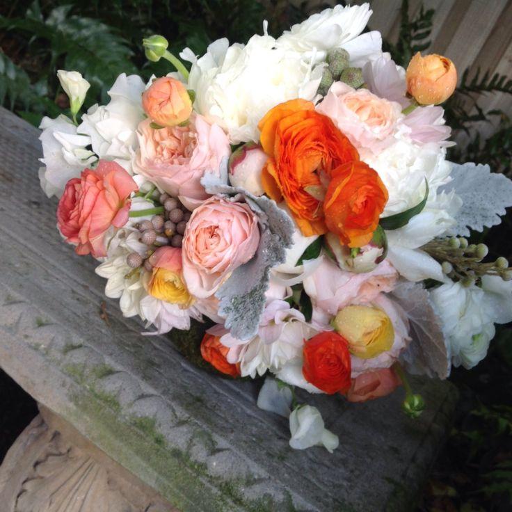 Florida citrus bride's bouquet of orange, peach and pink ranunculus , peach garden roses, white peonies, cafe au lait dahlias, silver brunia and dusty miller.