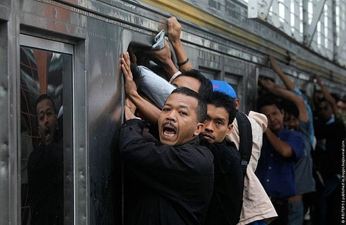 People hang onto a commuter train as they illegally ride the train which will transport them to Jakarta, in Depok, Indonesia's West Java province May 31, 2010. According to PT Kereta Api Indonesia, their trains operate 300 cars each day to serve about 500,000 commuters in Jakarta. In 2007 as many as 26 people were killed due to electricity shock and from falling off the roofs of trains. REUTERS/Crack Palinggi (INDONESIA - Tags: TRANSPORT BUSINESS SOCIETY)