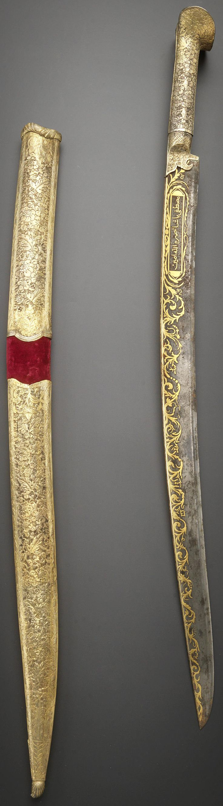 Ottoman yataghan / yatagan, circa 1800, slightly curving blade and tapering point, the spine and sides decorated with bands of gold overlay consisting of undulating leafy and floral vines, one side with an inscription-filled cartouche, the silver-gilt hilt and scabbard with repousse decoration consisting of profuse floral motifs, 76 cm. long. The inscriptions comprise: mustapha pasha nasarahu allal amin, 'Mustapha Pasha may Gold help him, Amen!'. www.ismailtuluce.com