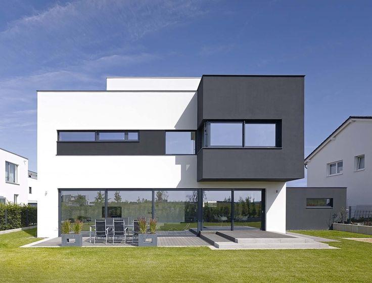 Blick auf die Fassade zum Garten. Schiebetüren, Massivverglasungen und Fensterleisten sorgen für einen horizontalen Schnitt in Schwarz und Weiß …
