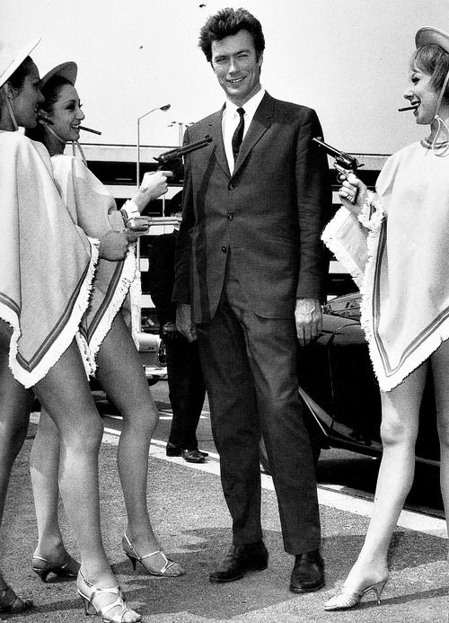 Clint Eastwood greeted at the airport by a bevy of gun-toting, poncho-wearing beauties as he promoted A Fistful of Dollars in London, 1967.