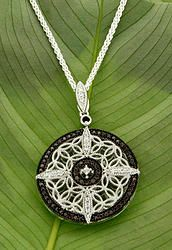 PPS0102 Keith Jack Round Night & Day PENDANT The fascination of the night sky – the brilliance of stars, delicate traces of the Milky Way, the infinite imaginings of space. A ring of chocolate colored zirconia surrounds a delicate silver filigree of trinity knots, and a starry compass of clear zirconia. Pendants are two sided. It reverses to the brilliance of sunlight sparkling on the water. Sterling Silver.