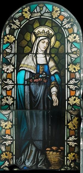 Stained Glass Window DESCRIPTION: This stained glass window depicts St. Elizabeth of Hungary holding a bouquet of flowers.