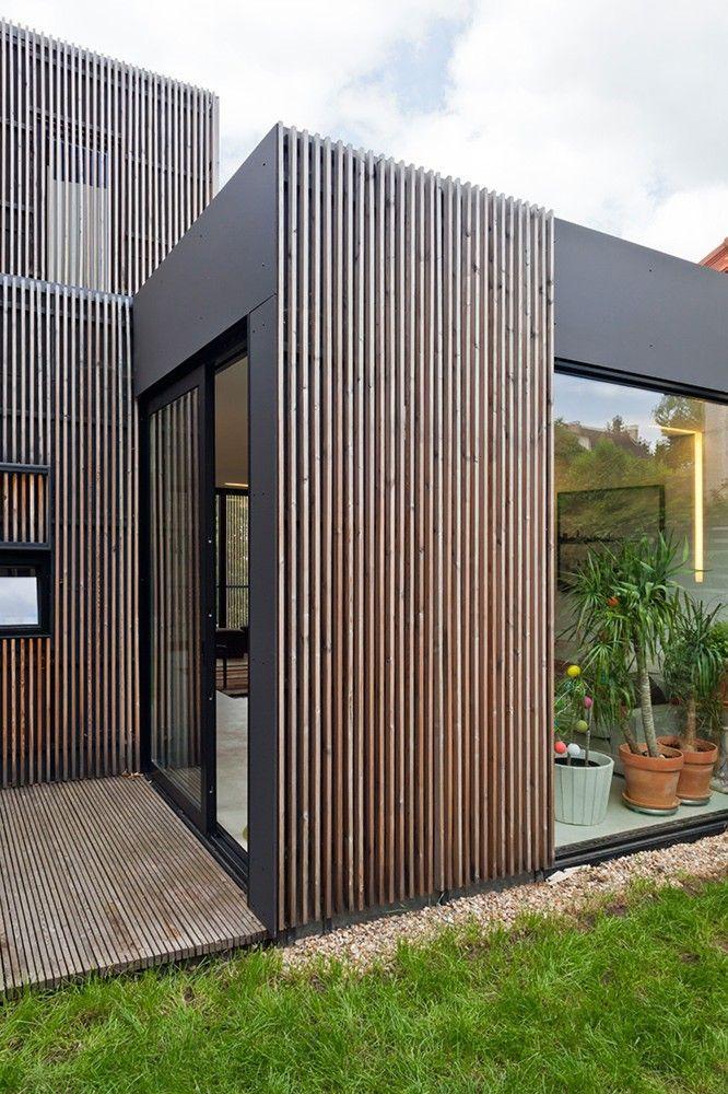 L'habillage extérieur combine dans ce cas des panneaux de fibro-ciment peints et des lames de bois. Les lames de bois sont plus épaisses que larges et sont posées à claire-voie
