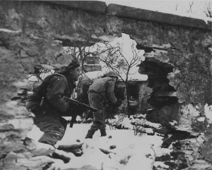 American soldiers march toward Wiltz, determined to fight back and reclaim the territory they lost.   Wiltz, Belgium. Circa December, 1944 - January, 1945.