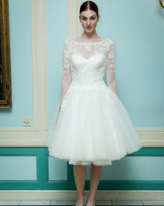 An iIllusion sweetheart neckline dress with long sleeves, a short full tulle skirt with a draped bodice. The dress has placed sequin and lace applique with touches of hand beading.