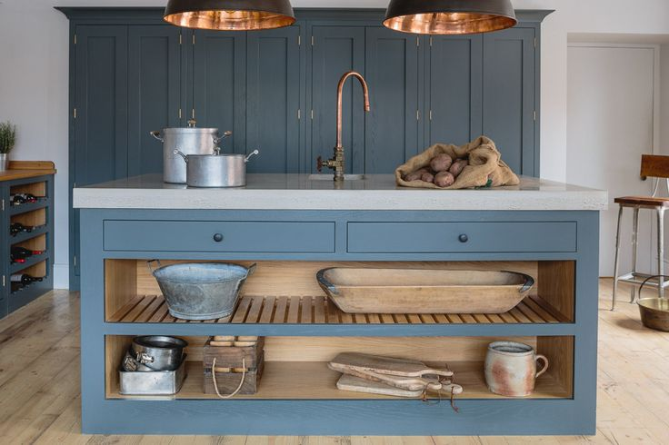 Sustainable Kitchens Showroom. Farrow & Ball Down Pipe painted oak cabinets in an industrial shaker style showroom kitchen. The island has a polished concrete worktop and open shelving with slatted wood. The hanging industrial pendant lights from Original BTC and the bespoke copper tap adds continuity to the space. The floors are made from reclaimed scaffold planks.