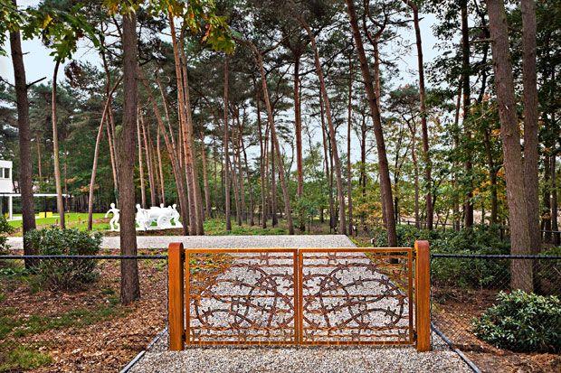 L'ingresso della casa a Bergeijk con il cancello Barbed Wire Gate disegnato da Studio Job, il vialetto di ghiaia e la scultura Food Cart lunga sei metri, creazione di Joep van Lieshout