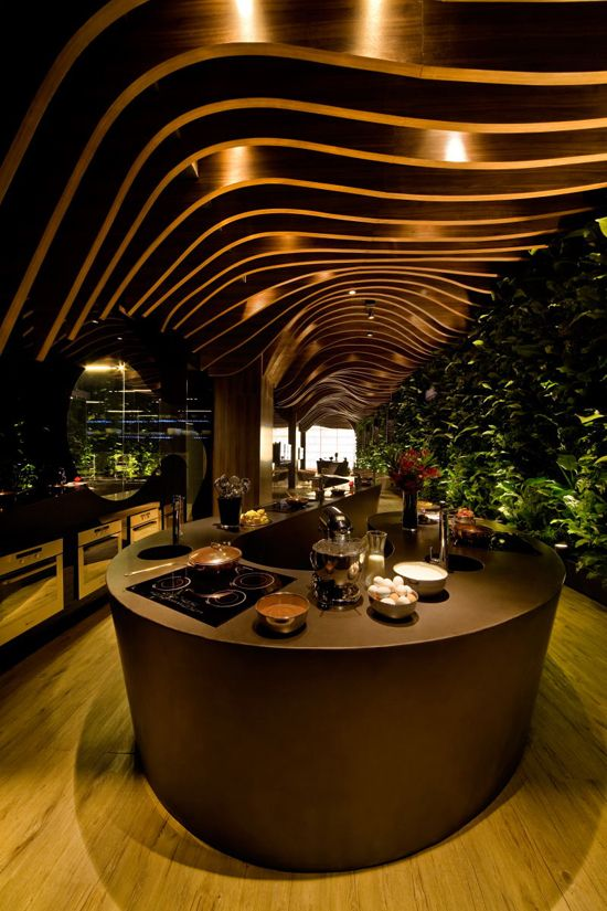 The wooden ceiling creates a beautiful sense of movement with its undulating pattern of waves that rhythmically guide the light through the space.