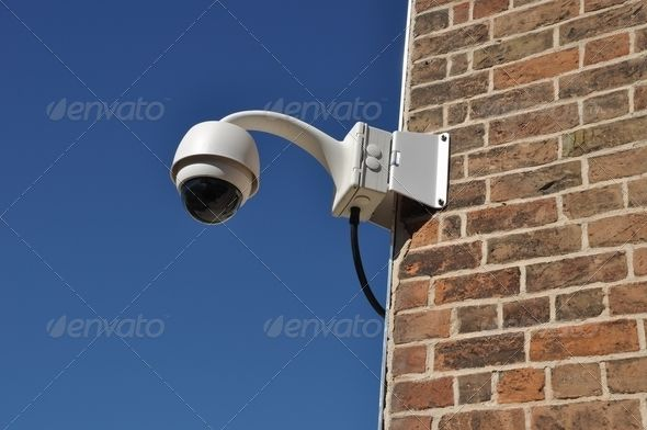 Surveillance camera attached on a brick wall building. http://photodune.net/item/security-camera/556789