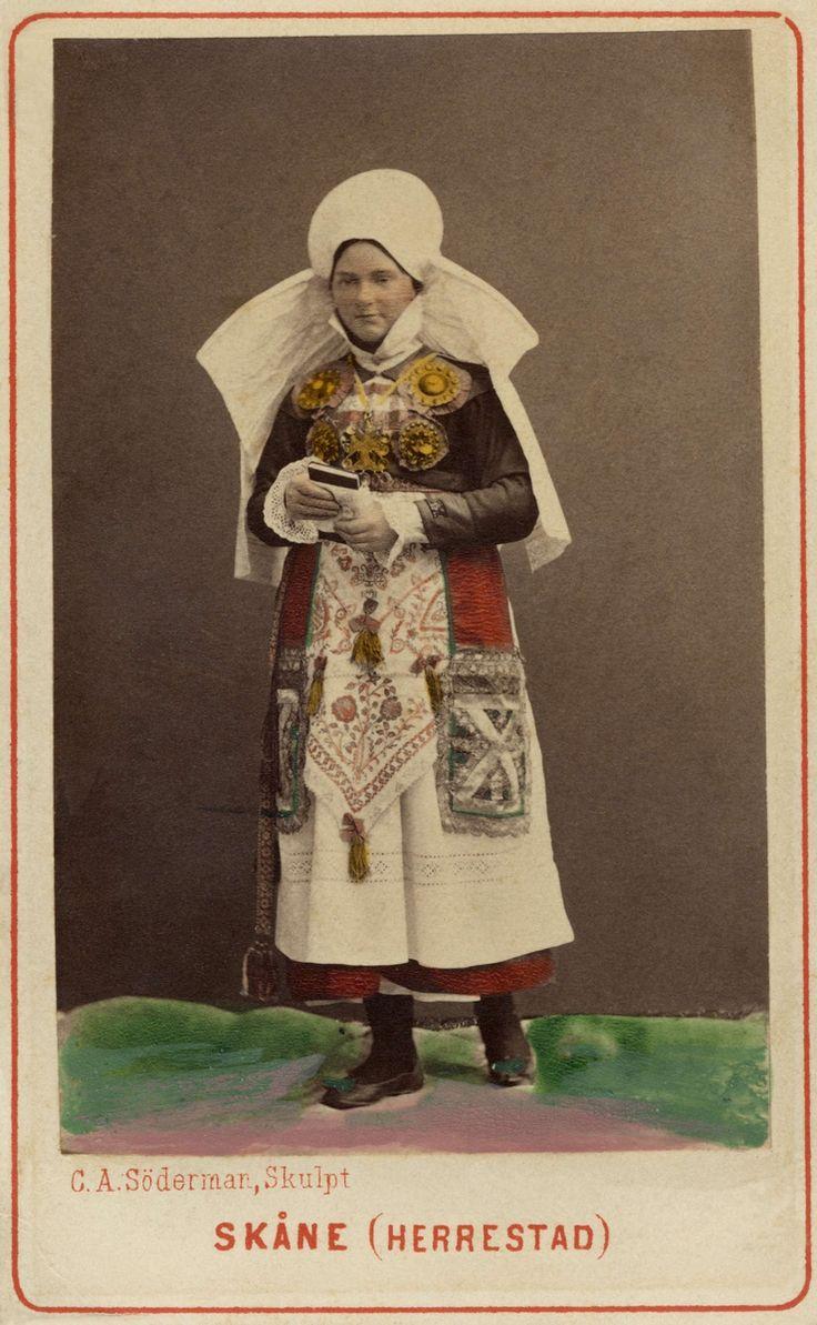 SE Herrestads hd. Dräktdocka med huvud skulpterat av C A Söderman, visa på världsutställningen i Paris 1867. Kvinna i dräkt från Herrestad, Skåne.Kolorerad.