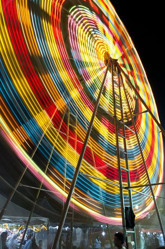 A slow shutter speed photo of a ferris wheel during the night with the pretty colours which makes it stand out, and it looks like it moving