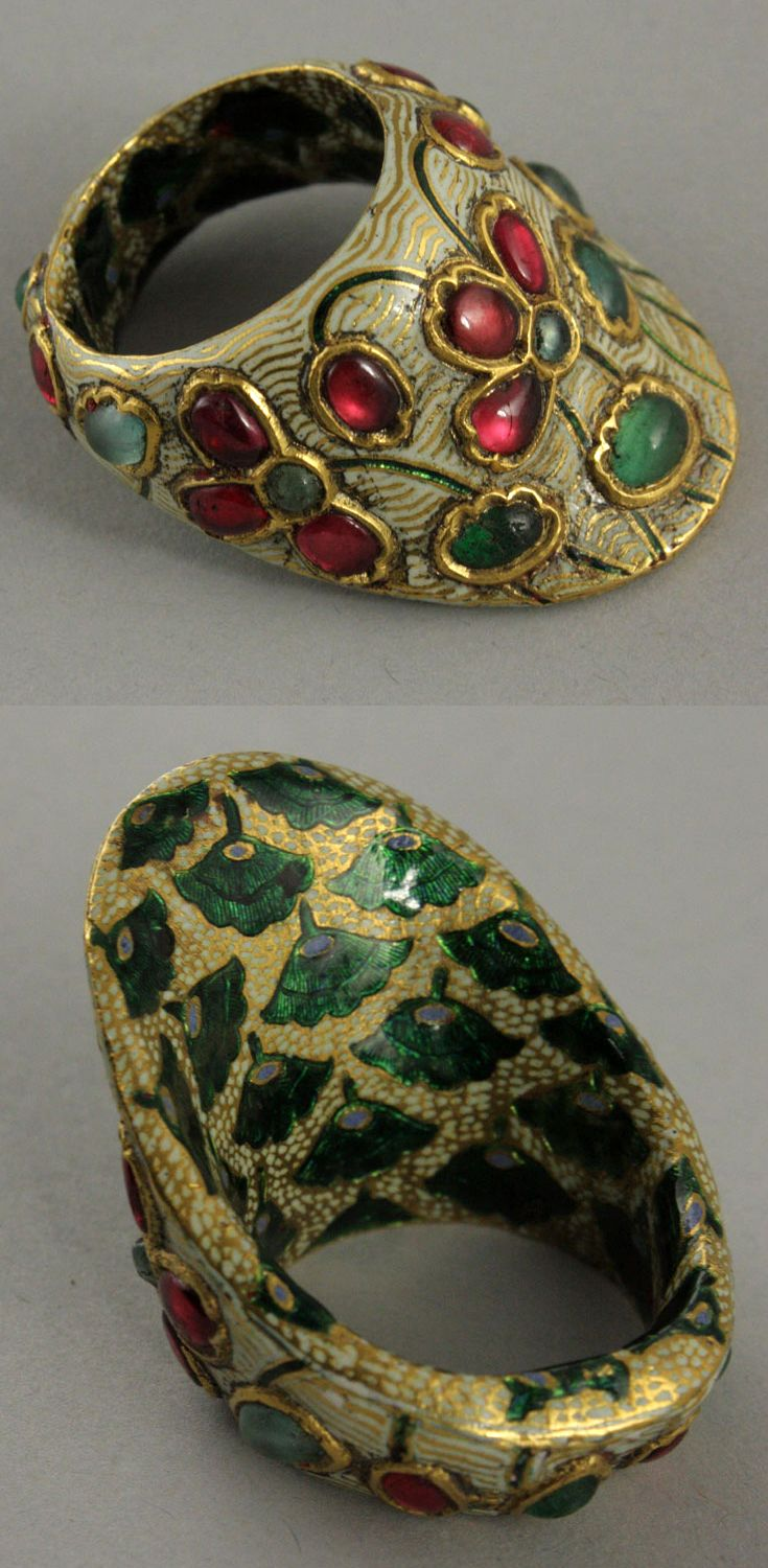 Northern India | Archer's thumb ring; gold set with rubies and emeralds, with white enamel lotus motifs. Green enamel lotus design on the inside.| 19th century